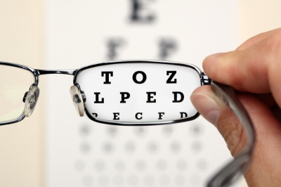 Pair of glasses focusing on letters to determine strength of vision