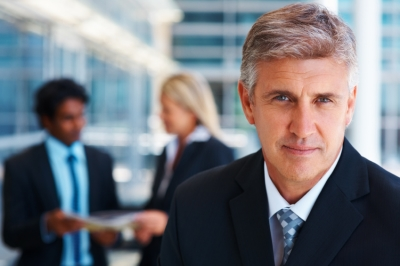 Businessman looking at the camera with other employees talking in the back