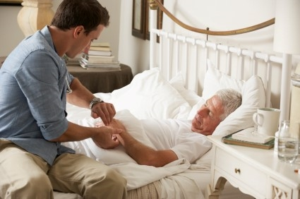 Sick older man in bed holding younger man's hand